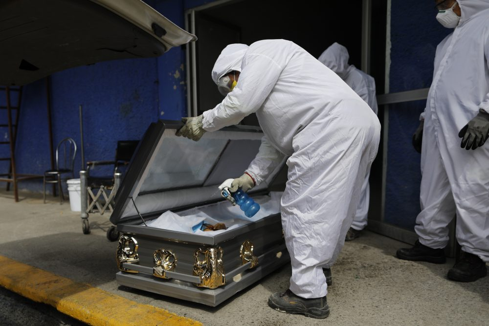 A worker sprays disinfectant solution inside the coffin of a person who died from suspected COVID-19, as the body arrives at the crematorium at Xilotepec Cemetery in Xochimilco, Mexico City, on Monday.