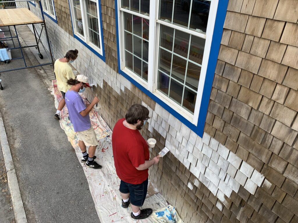 Project Interns work with AiA Mentor Artist Zack Winklhofer, center, to apply a base coat to the Main Street elevation of the Apprenticeshop in Rockland.