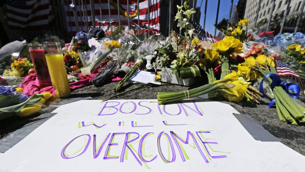 Flowers and signs adorn a barrier in 2013, two days after two explosions killed three and injured hundreds, at Boylston Street near the of finish line of the Boston Marathon at a makeshift memorial for victims and survivors of the bombing.
