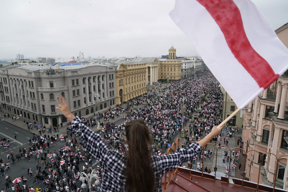 A woman waves an old Belarusian national flag standing on the roof as Belarusian opposition supporters march on Aug. 3 to Independence Square in Minsk, Belarus.