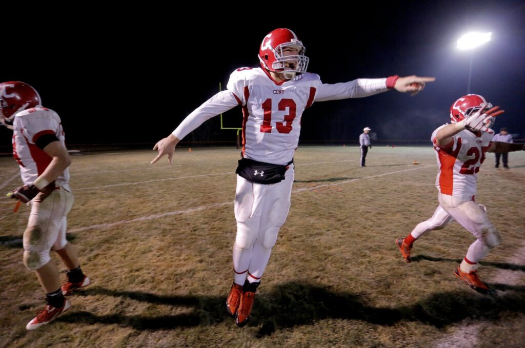 Cony quarterback Ben Lucas, center, leaps in celebration after defeating Brunswick to capture the Eastern Class B semifinal on Nov. 15, 2013.