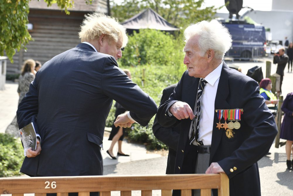 Britain's Prime Minister Boris Johnson greets veteran Bill Redston following the national service of remembrance marking the 75th anniversary of V-J Day at the National Memorial Arboretum in Alrewas, England, on Saturday.