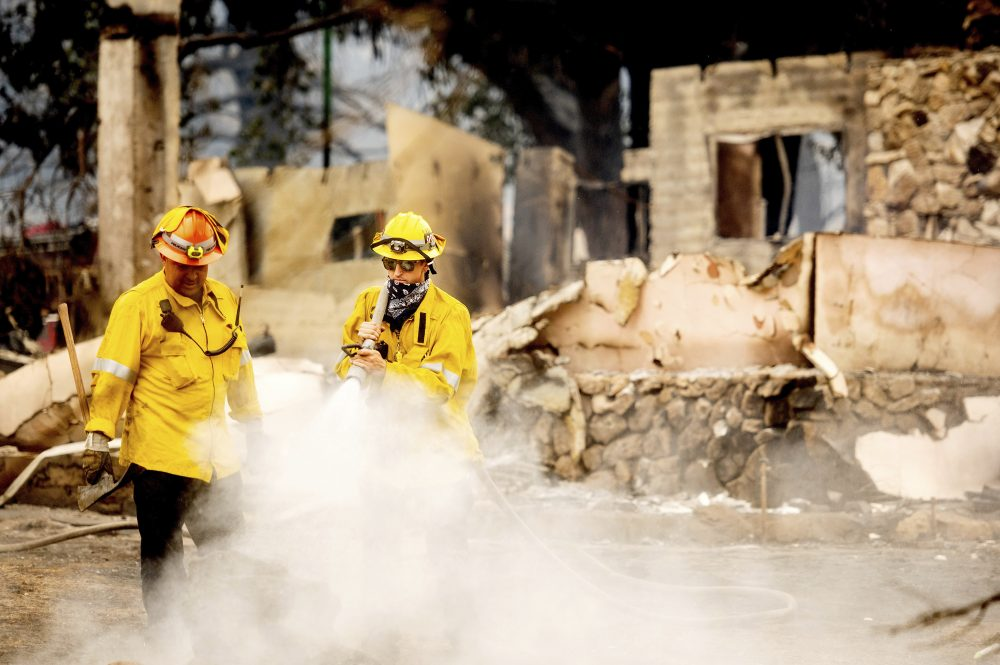 A Los Angeles County firefighter extinguishes hot spots at a scorched residence while battling the Lake Fire in the Angeles National Forest, Calif., north of Santa Clarita on Thursday.