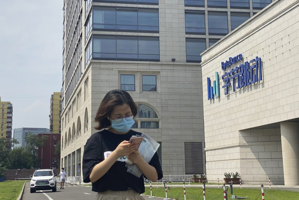 A woman passes by the ByteDance headquarters in Beijing. The Chinese government is complicating the U.S.-government-ordered sale of U.S. TikTok assets.  China on Friday introduced export restrictions on artificial intelligence technology, seemingly including the type that TikTok uses to choose which videos to spool up to its users.