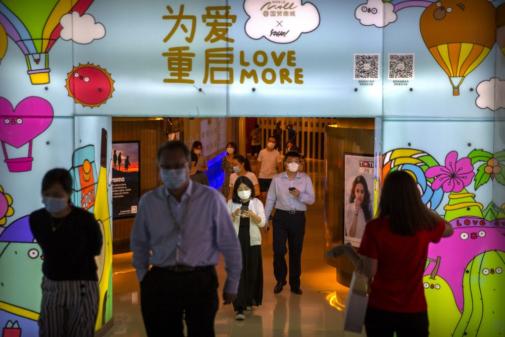 """People wearing face masks to protect against the coronavirus walk through a shopping mall in Beijing on Aug. 14. Today's guest columinst writes: """" ... COVID-19 has shown us that our world is connected more than ever by transportation and technology, so we must work with each other better than ever. ..."""""""