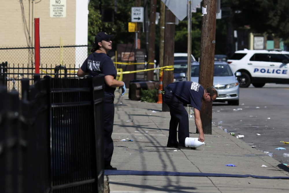 Cincinnati firefighters use bleach to clean and remove pools of blood left at the scene of a mass shooting near Grant Park in the Over-the-Rhine neighborhood of Cincinnati on Sunday.