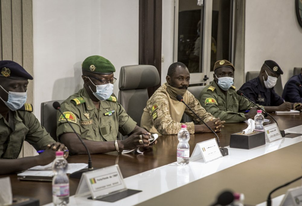 Col. Assimi Goita, center, who has declared himself the leader of the National Committee for the Salvation of the People, is accompanied by group spokesman Ismael Wague, left, and group member Malick Diaw, center-left, as they meet with a high-level delegation from the West African regional bloc known as ECOWAS, at the Ministry of Defense in Bamako, Mali, Saturday.