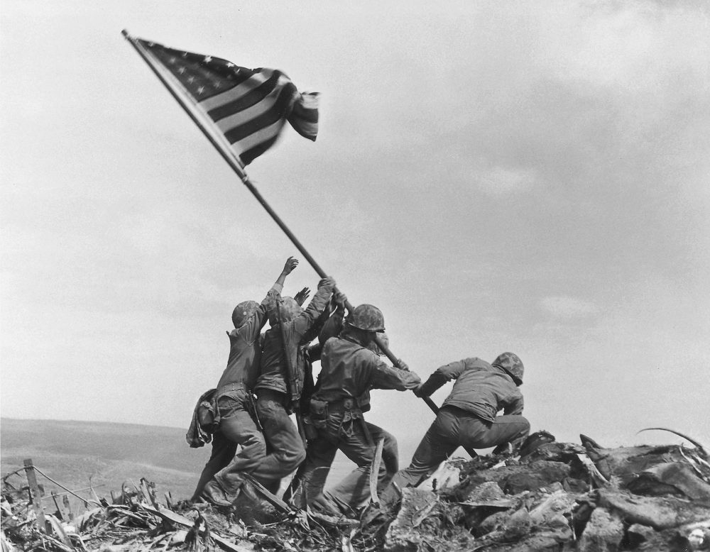 U.S. Marines of the 28th Regiment, 5th Division, raise an American flag atop Mount Suribachi, Iwo Jima, Japan, on Feb. 23, 1945. Strategically located only 660 miles from Tokyo, the Pacific island became the site of one of the bloodiest, most famous battles of World War II against Japan.