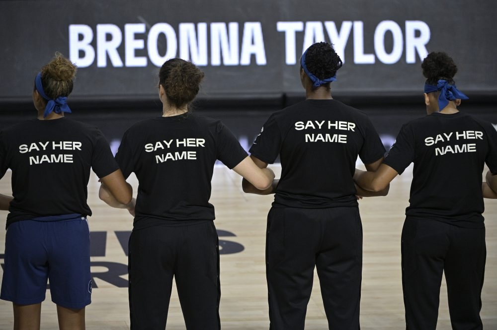 Minnesota Lynx players lock arms during a moment of silence in honor of Breonna Taylor before a WNBA basketball game against the Connecticut Sun on  July 26 in Bradenton, Fla.