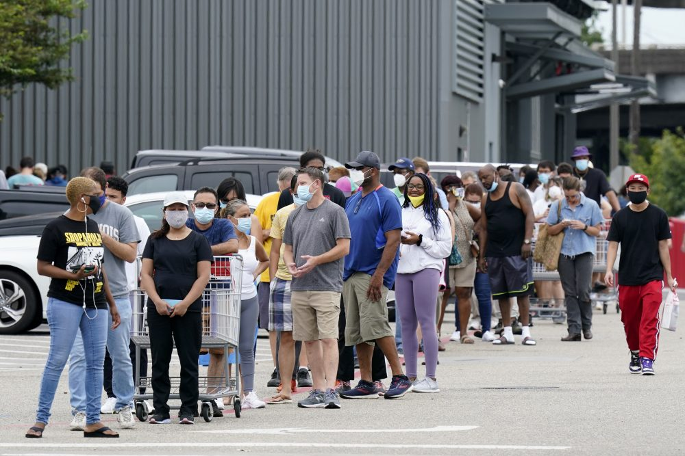 People line up to enter retail chain Costco to buy provisions Sunday in New Orleans, in advance of Hurricane Marco, expected to make landfall on the Southern Louisiana coast.