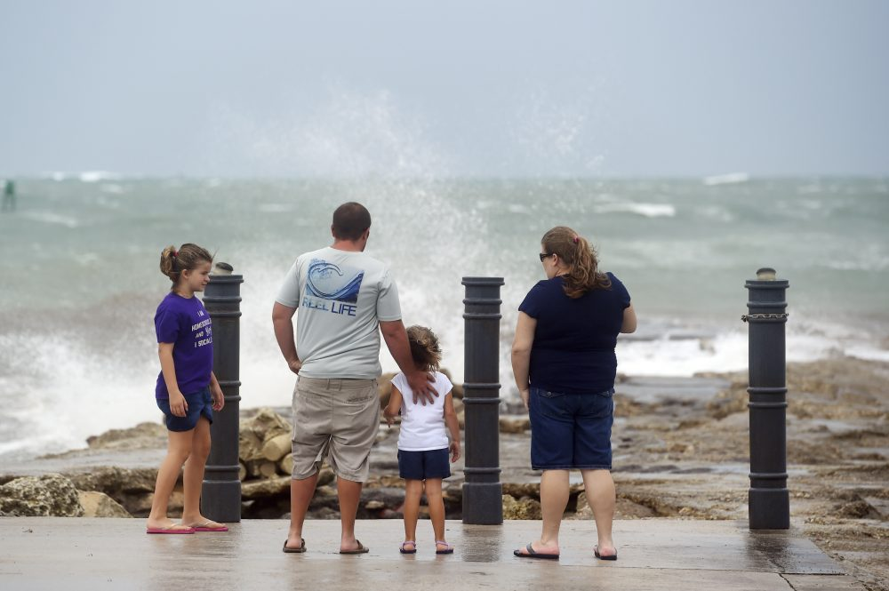 Elizabeth Whittemore (from left), along with her father James, sister Jordan and mother Susan, stand at the end of the South Jetty in Fort Pierce on Sunday, watching the waves crash over the rocks brought by the high winds of Tropical Storm Isaias churning off the coast.