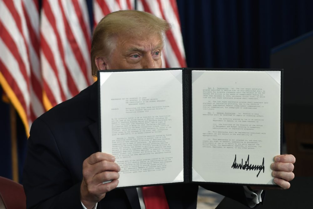 President Trump signs an executive order during a news conference Saturday at the Trump National Golf Club in Bedminster, N.J.