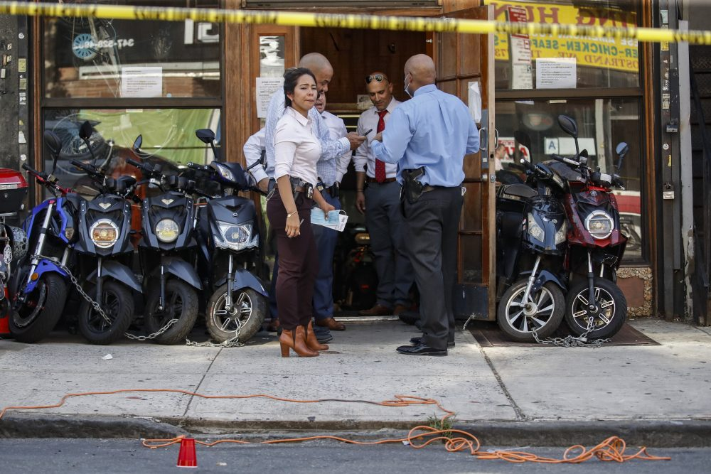 Police officers respond to a crime scene on Nostrand Avenue, where a 23-year-old man was discovered with gunshot wounds to his legs and torso before being transported to a hospital where he died from his injuries, in the Brooklyn borough of New York on July 18.