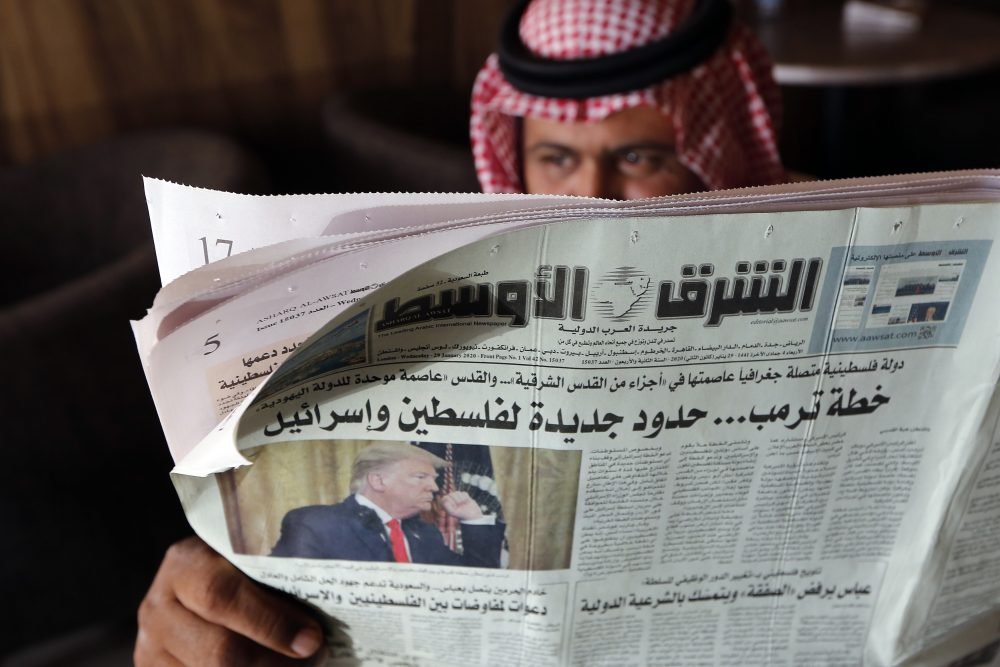 A man holds the daily Asharq Al-Awsat newspaper, fronted by a picture of President Trump, Jan. 29 at a coffee shop in Jiddah, Saudi Arabia. The agreement between the United Arab Emirates and Israel to establish full diplomatic ties comes as little surprise to those closely following the nuances of Middle East politics, and Trump administration's almost single-minded push to broker a deal of this kind without a resolution first to the Israeli-Palestinian conflict.