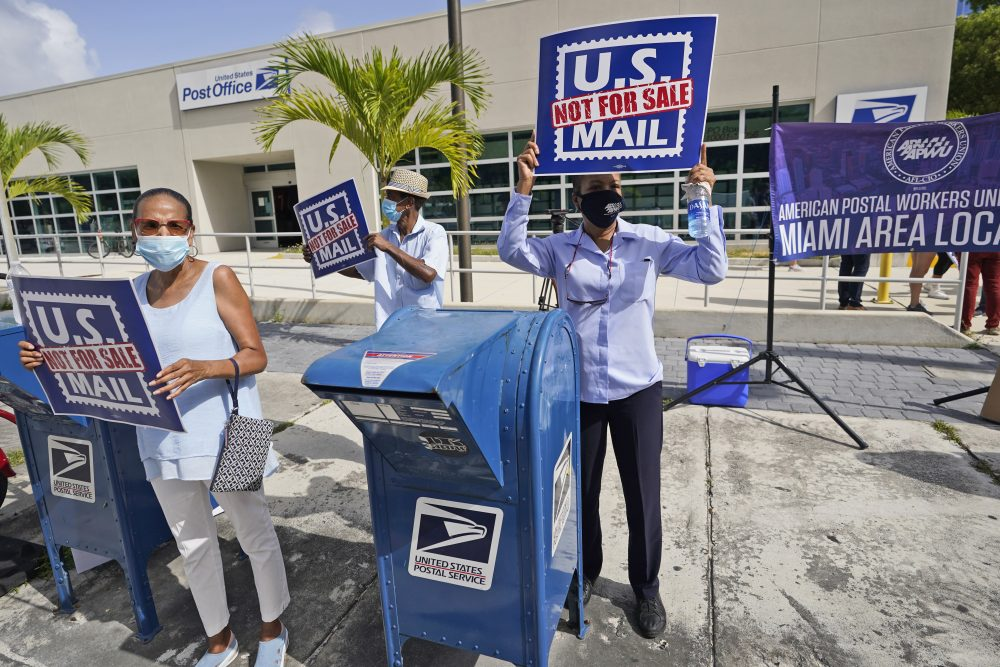 """Protesters demonstrate during a National Day of Action to Save the Peoples Post Office! outside the Flagler Station post office in August in Miami. A federal judge found Thursday that President Trump and the U.S. Postal Service chief """"are involved in a politically motivated attack on the efficiency of the Postal Service."""""""