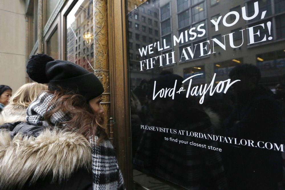 Women peer in the front door of Lord & Taylor's flagship Fifth Avenue store which closed for good in New York in 2019.