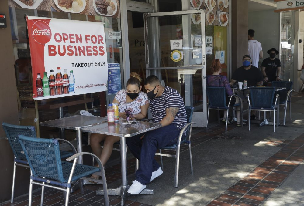 Josefina Pacheco, front left, and her husband Norberto wait to have a meal served outside at a restaurant in Burbank, Calif., in July. Restaurant chains are reporting they're paying more, but that doesn't mean they're filling their staff openings.