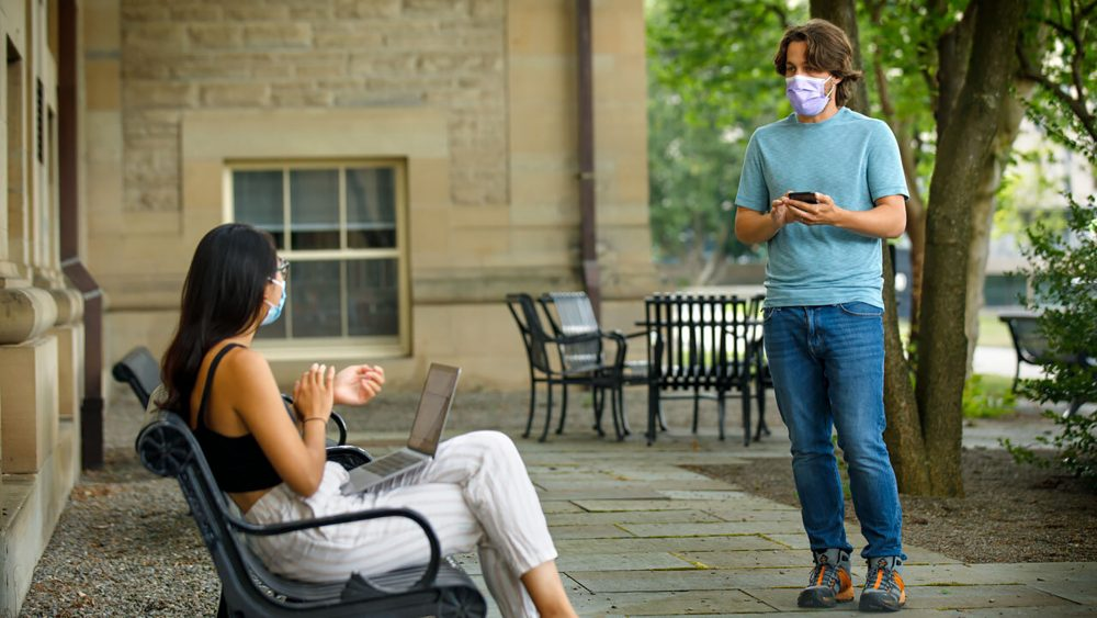 Bryan Maley, right, a grad student in the Master of Public Health program, interviews a student on campus about mask-wearing experiences as part of a public health survey, July 30 in Ithaca, N.Y.