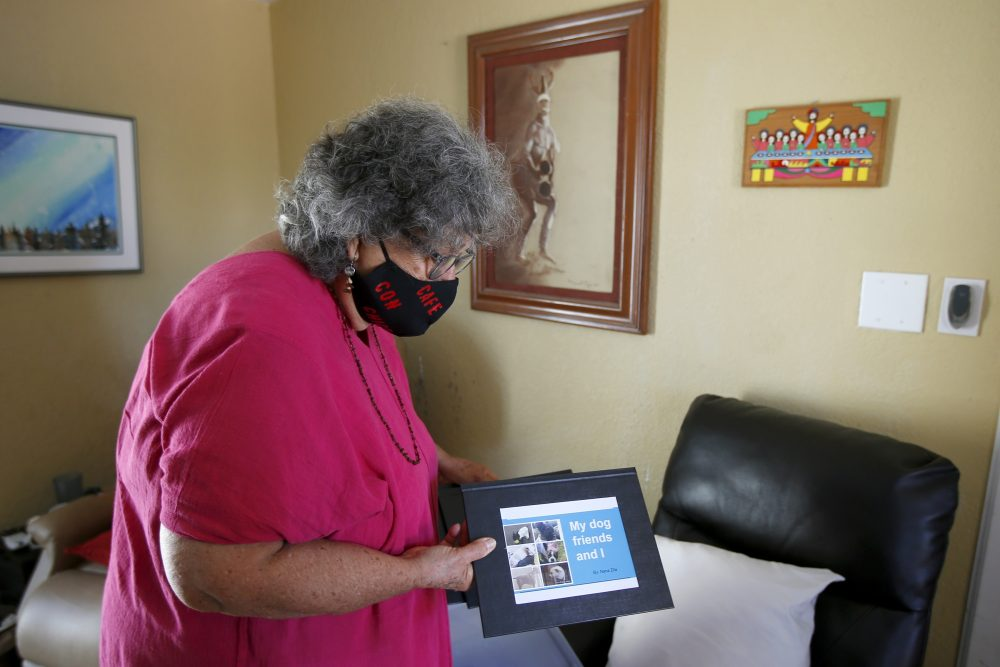 """Zita Robinson, who's 77 and diabetic, and has been careful around her granddaughter amid the coronavirus pandemic, shows a book she made for her granddaughter, 8-year-old Traris """"Trary"""" Robinson-Newman."""