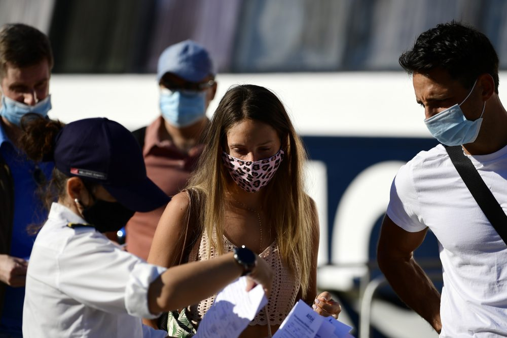 A ship company worker checks passengers' health questionnaires prior to their boarding, at the port of Piraeus, near Athens, on Sunday