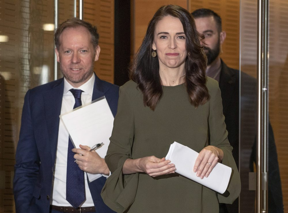 New Zealand Prime Minister Jacinda Ardern, center, arrives to announce a new date for national elections, at a news conference in Wellington, New Zealand, on Monday. The election had been scheduled for Sept. 19 but will now be held on Oct. 17, after a COVID-19 outbreak in Auckland.