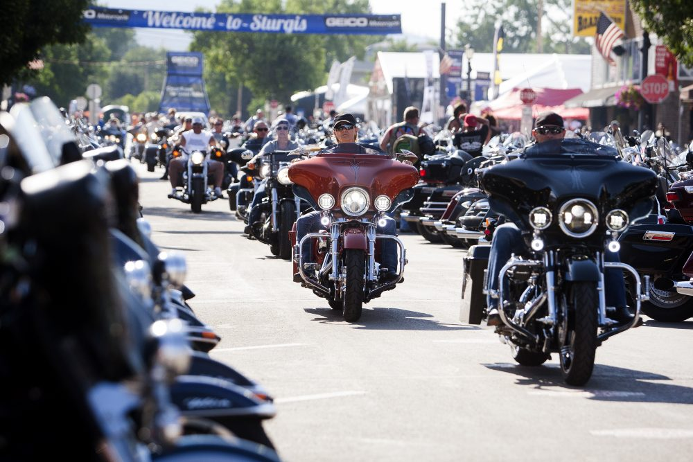 Bikers ride down Main Street in downtown Sturgis, S.D., before the 76th Sturgis motorcycle rally officially begins.  South Dakota, which has seen an uptick in coronavirus infections in recent weeks, is bracing to host hundreds of thousands of bikers for the 80th edition of the Sturgis Motorcycle Rally.