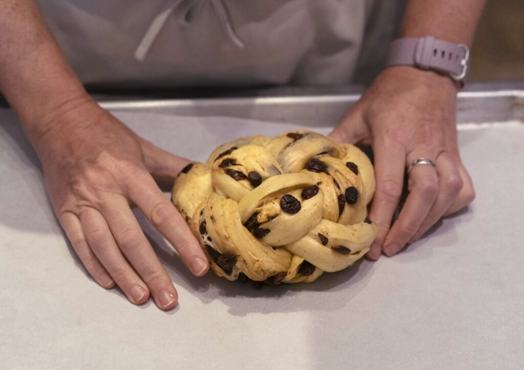 Tin Pan Bakery owner and chief baker Elise Richer places a special round Rosh Hashanah challah on a baking sheet before its second rise.