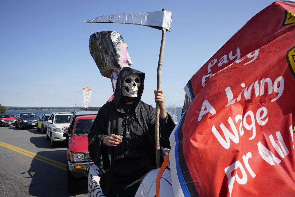 Dressed as the Grim Reaper, Asher Platts, a volunteer with the Southern Maine Workers' Center, stands in the back of a truck as a caravan leaves the Eastern Promenade in Portland on Monday, Labor Day. Organizers dubbed the caravan a funeral procession because of the number of workers who have died of COVID-19.