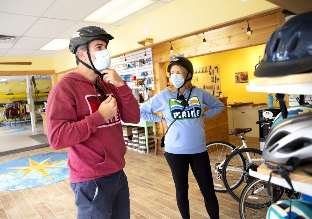 Laura and Mark Kiely try on helmets as they rent bikes from Coastal Maine Kayak and Bike in Kennebunk on Friday. The couple from Philadelphia are visiting Maine for their first time and have gone to Bar Harbor, Portland and Kennebunkport. (Staff photo by Derek Davis/Staff Photographer)