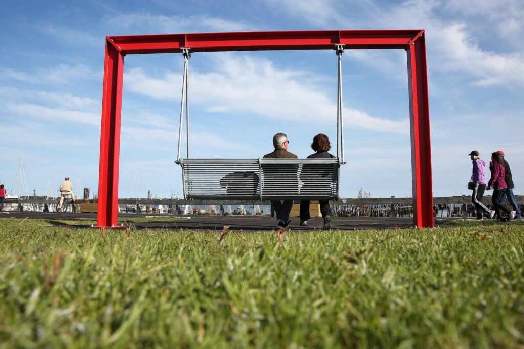 Kirk and Sara Reichard of Chester County, Pa., sit in one of two swings at a new park that opened Friday on Amethyst Lot in Portland. The waterfront park is next to Eastern Prom Trail and Ocean Gateway.  Ben McCanna/Staff Photographer