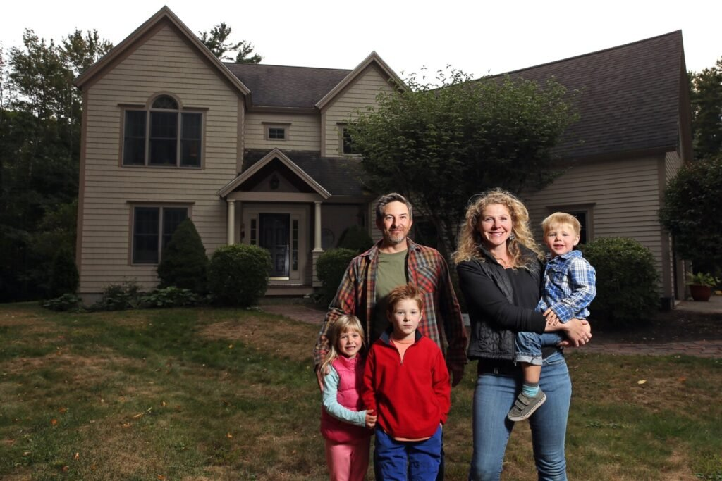 Matt and Elli Carter and their children, Maeve, left, Alden and Reed in front of the home in Cape Elizabeth they bought this summer. Low interest rates and rising prices allowed the Carters to refinance their home just four months after they bought it.