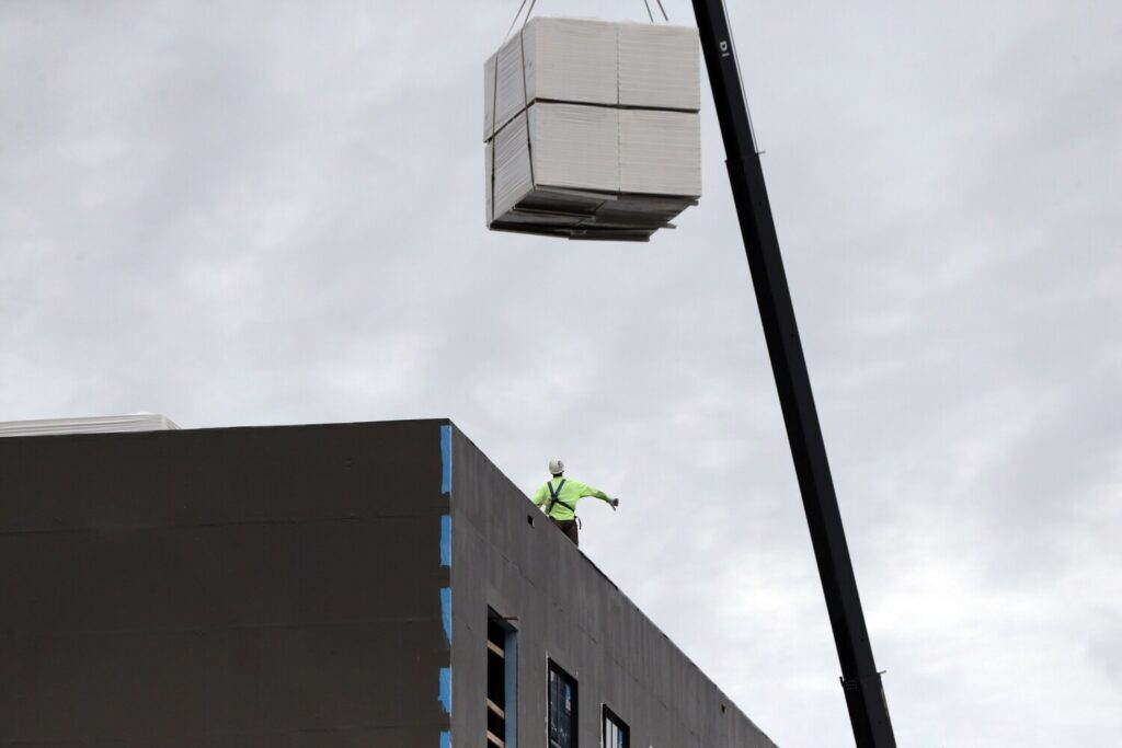 A worker makes hand signals to a crane operator lowering materials onto the roof of a building under construction at the corner of Commercial and Center streets in Portland on Sept. 2. Construction has been one of the remaining bright spots in Maine's struggling economy.