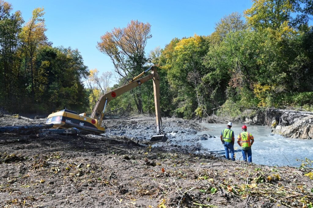 A crew with Shaw Brothers use an excavator to move debris to open up the channel of the Presumpscot River in Westbrook Tuesday. A large landslide completely blocked the Presumpscot River in Westbrook earlier this month.
