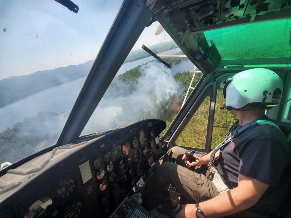 Maine Forest Ranger Jeff Miller  surveys a fire near Moosehead Lake this summer, one of more than 900 so far this year in the state.