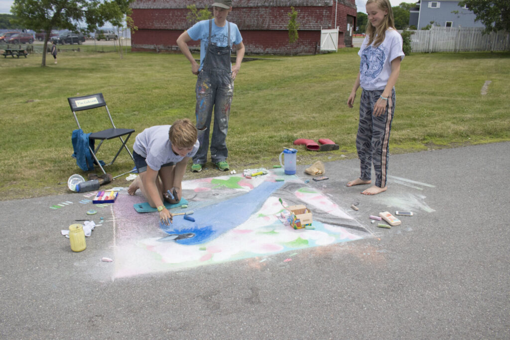 Bridget Matros, Kids & Families Programs manager at Waterfall Arts, left, with two participants in Heritage Park during the 2017 Chalk Walk.