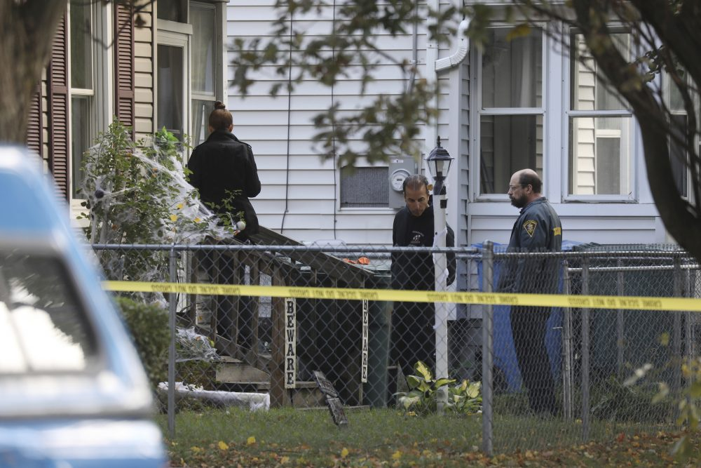 Rochester police look over the area of a home after a fatal shooting at a backyard party, on Saturday in Rochester, N.Y. Police are still trying to piece together who opened fire and why.