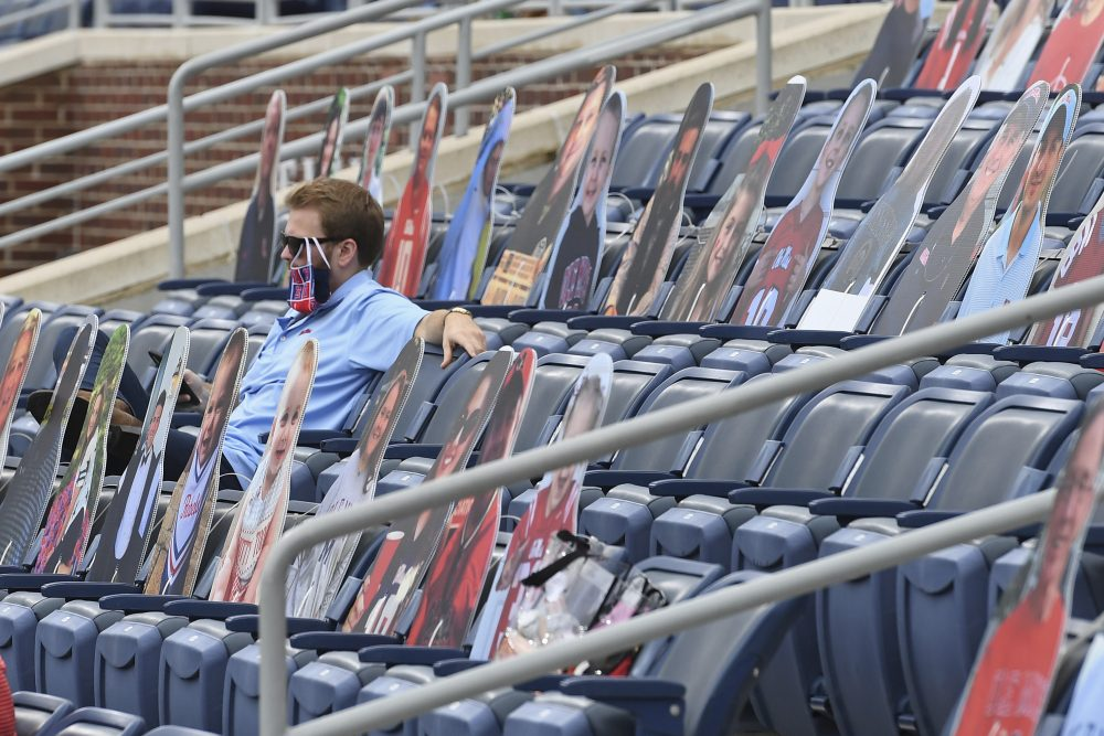 A fan sits among cardboard cutouts of other fans before the first half of an NCAA college football game between Mississippi and Florida in Oxford, Miss., on Saturday. Thomas Graning/Associated Press