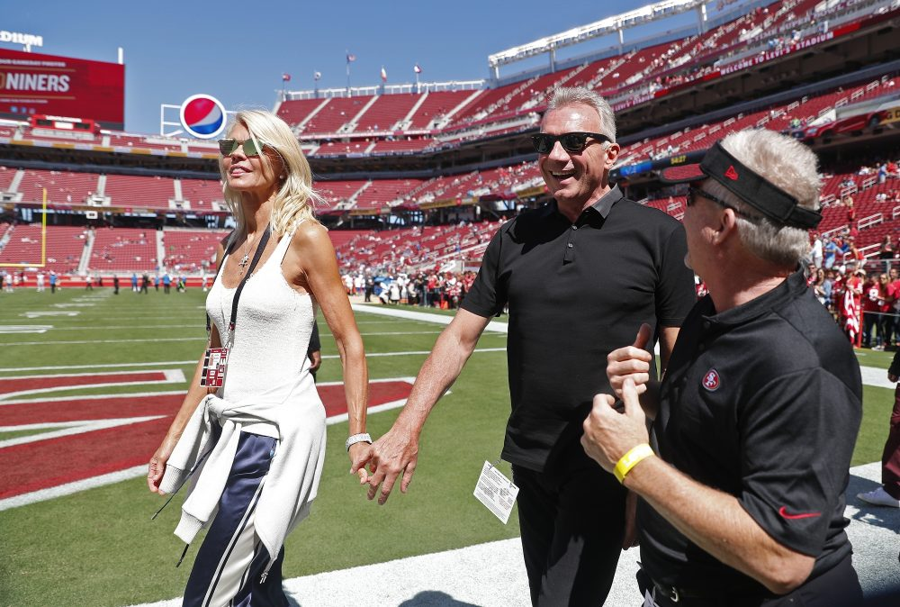 Joe Montana and his wife, left, Jennifer walk onto the field at Levi's Stadium Sept. 16, 2018,  before an NFL football game between the San Francisco 49ers and the Detroit Lions in Santa Clara, Calif.