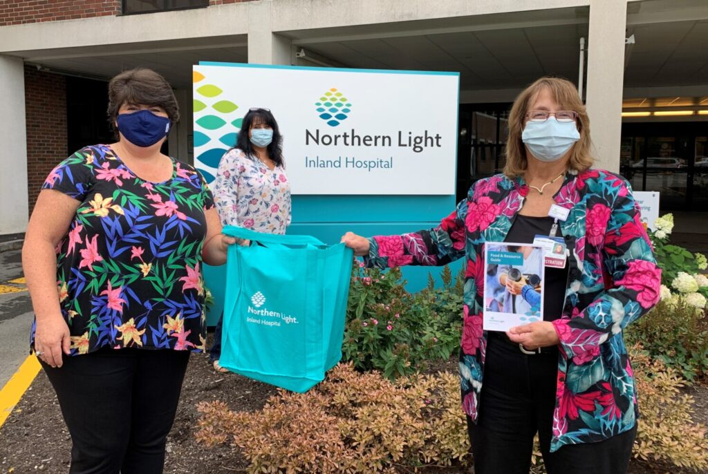 From left, Joanne Booth, Sodexo senior manager; Bridgette Gemelli, community health navigator; and Terri Vieira, president of Inland Hospital, hold an emergency food bag and a Food Resource Guide.