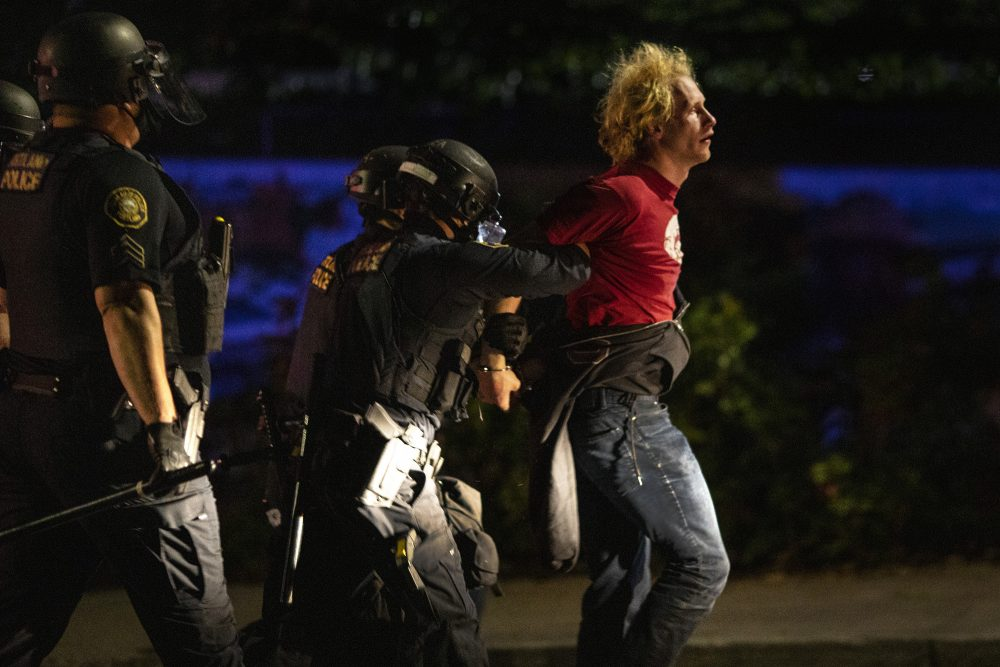 Portland police make arrests during the nightly protests at a Portland police precinct on Sunday in Portland, Ore. Oregon State Police will return to Portland to help local authorities after the fatal shooting of a man following clashes between President Trump supporters and counter-protesters that led to an argument between the president and the city's mayor over who was to blame for the violence.
