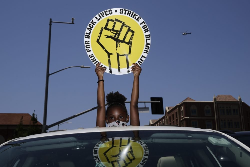 Audrey Reed, 8, holds up a sign through the sunroof of a car during a July 20 rally in Los Angeles.