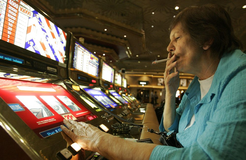 Judy King of Daytona Beach, Fla., holds her cigarette while playing a slot machine at the MGM Grand in Las Vegas in 2005. One of the last Vegas Strip resorts to reopen after coronavirus closures will be the first to be smoke-free, MGM Resorts International announced Monday.