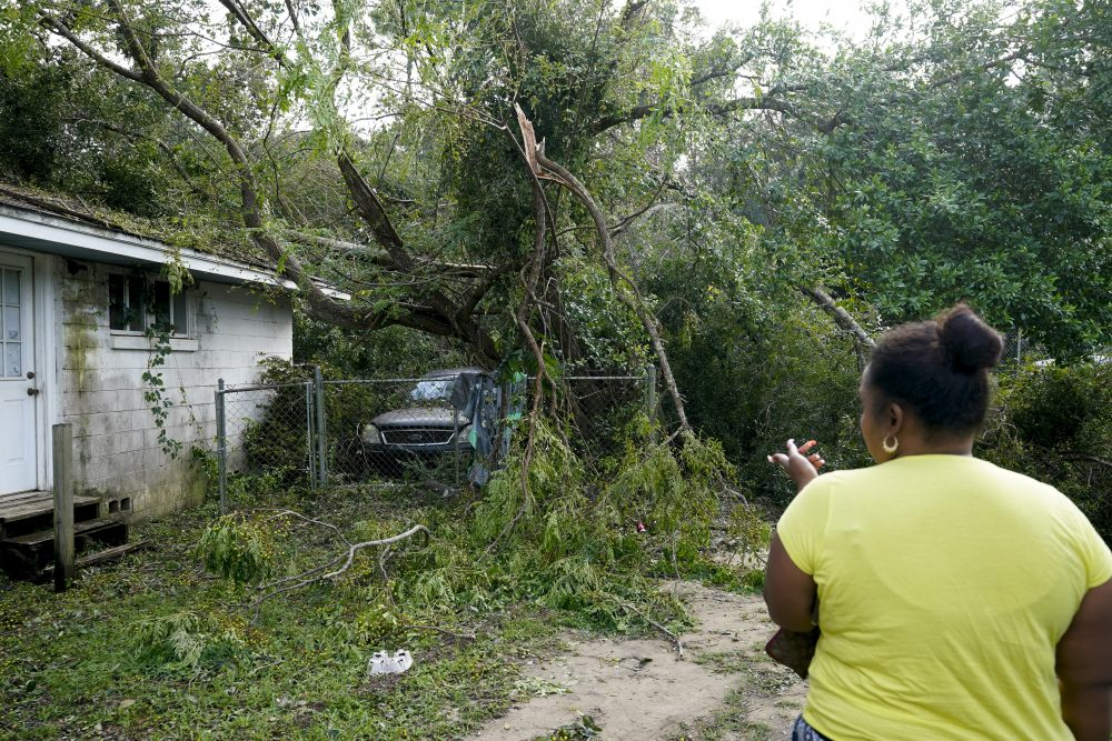 Seleka Souls looks over a neighbor's home that was damaged by Hurricane Sally, on Friday in Pensacola, Fla.