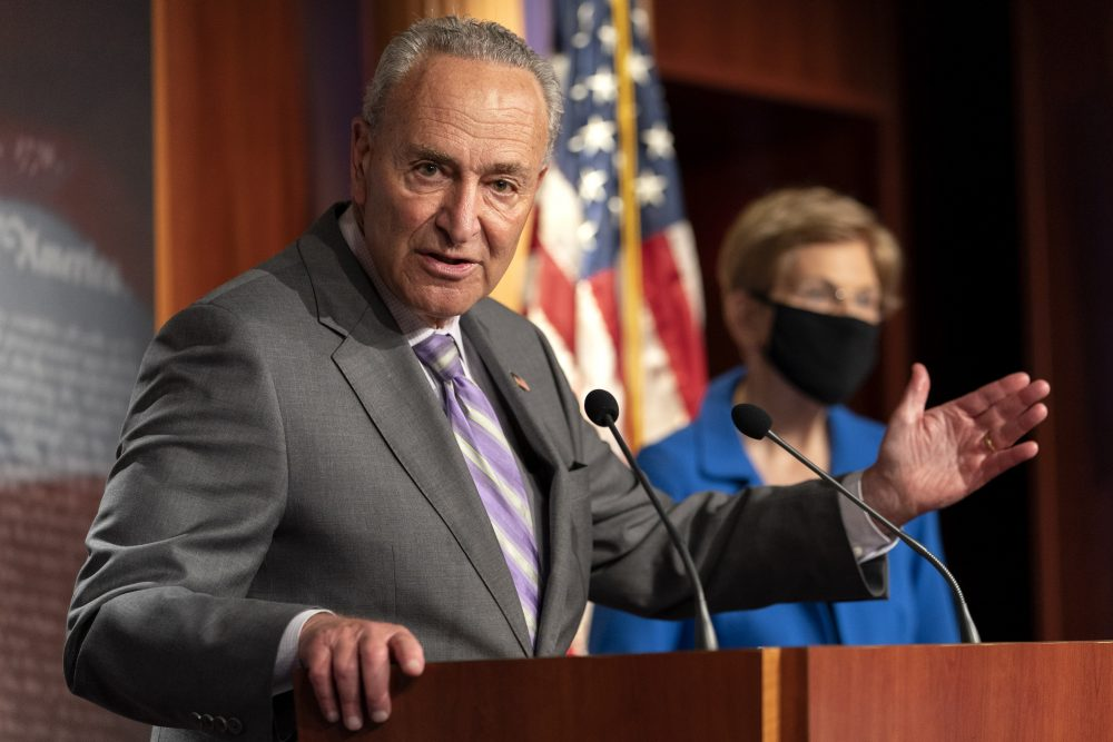 Senate Minority Leader Sen. Chuck Schumer of N.Y., left, with Sen. Elizabeth Warren, D-Mass., speaks during a news conference Wednesday on Capitol Hill in Washington.