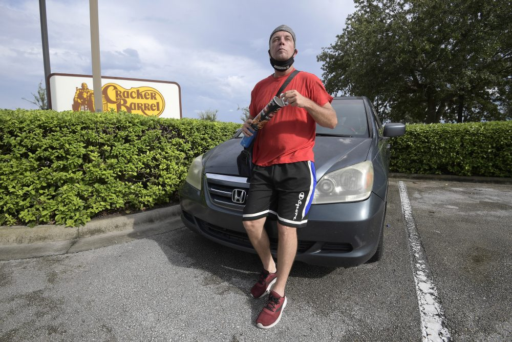 Jeff Lello stands in front of the van in which he lives, in the parking lot of a Cracker Barrel restaurant. He became homeless after being laid off from his job as a waiter at an Orlando, Fla., restaurant because of the pandemic. (AP Photo/Phelan M. Ebenhack)