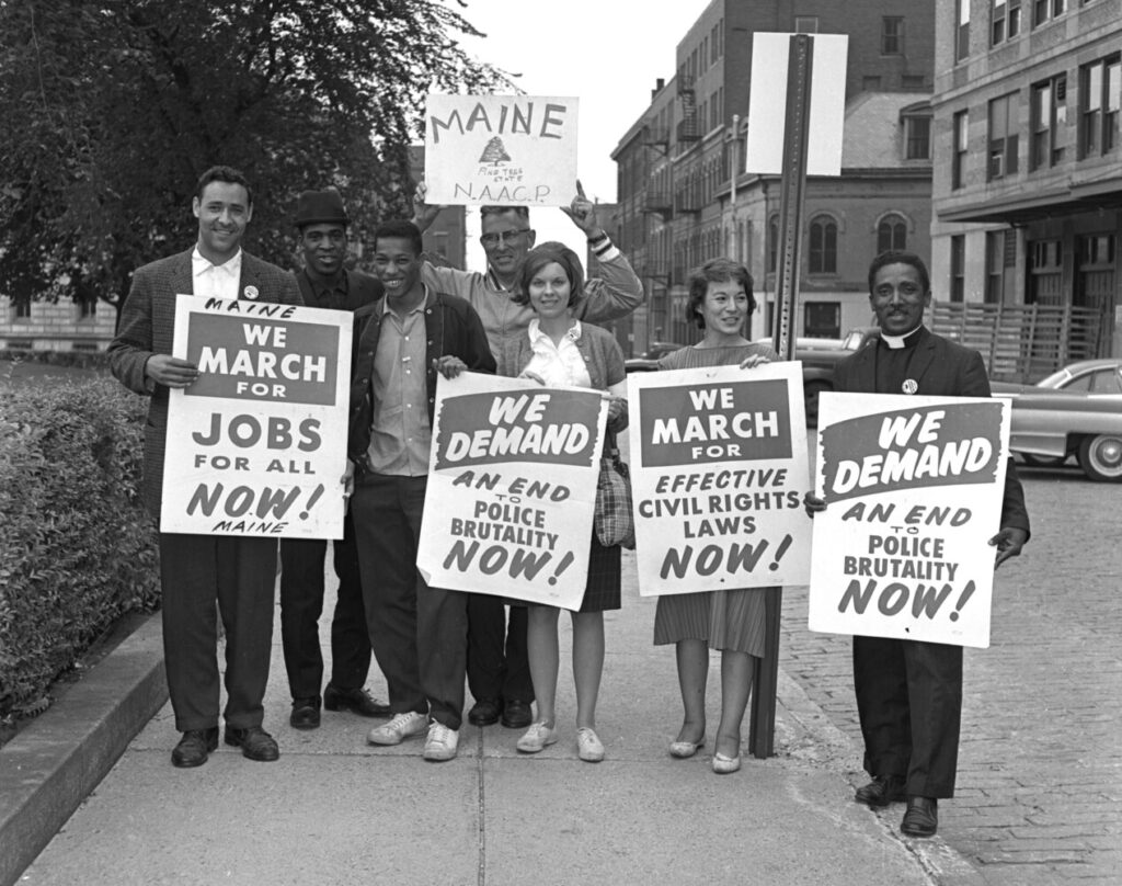 In August 1963, Gerald Talbot stands at left on Market Street with other Mainers who took part in the March on Washington. Left to right: Gerald Talbot, Alfred Burris, Lawrence Graham, Reverend Valton V. Morse, Elizabeth Aldrich, Mrs. Joseph Robey, Reverend John C. Bruce