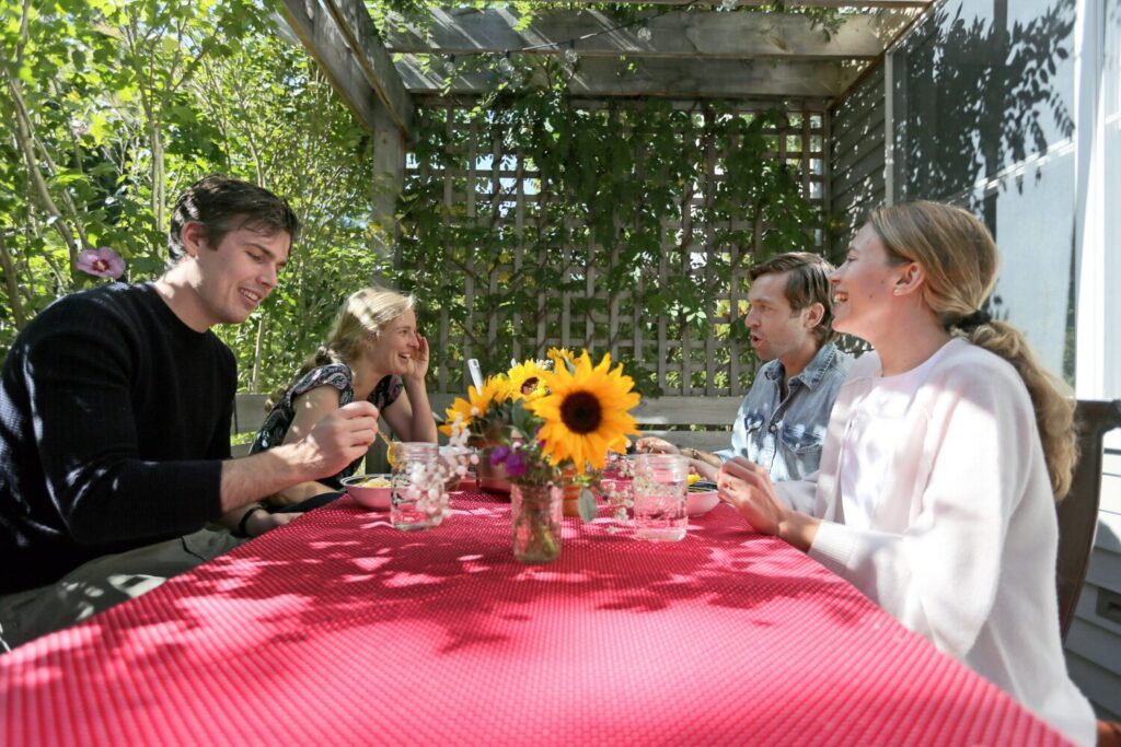 "Portland housemates Eoghan Sweeney, left, Kat McNeil, Andrew Tufts and Anna Ackerman, all of whom work remotely at least in part, prepare to eat lunch together on their back deck. Sharing a mid-day meal, getting to hear ""snippets"" of each other's days, has been a pleasure of working from home, said Ackerman."