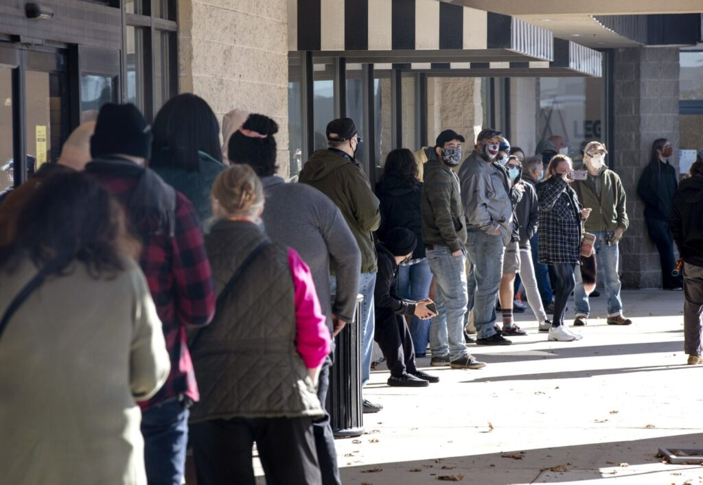 People line up outside Theory Wellness on Friday, just minutes before the store opens to the public for the first day of recreational marijuana sales in Maine.