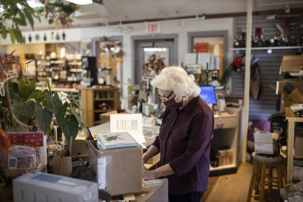 Rhoda Dillman works behind the counter at Casco Bay Cutlery & Kitchenware in Freeport. The Dillmans, who have owned the store for decades, said they have remained busy during the pandemic.
