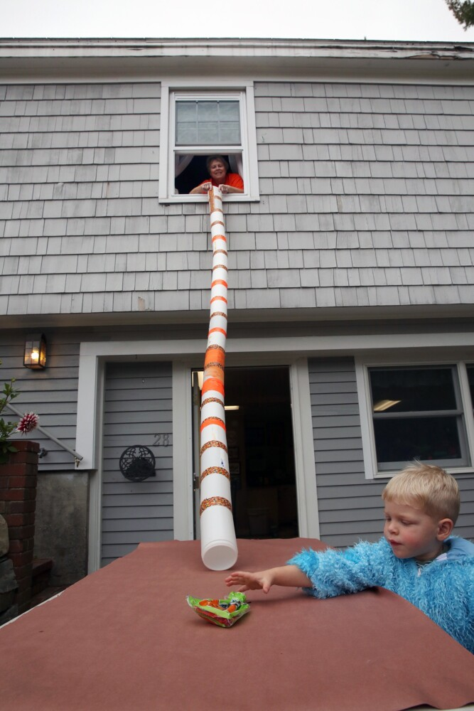 Julie Otte of Cumberland and her grandson Logan Otte, 2, demonstrate a 10-foot-long candy chute made with Clorox wipes containers and candy corn duct tape.